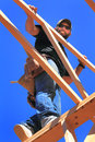 Framer at work a carpenter wearing leather nail bags looking down standing in the rafters working on the roof of a house that is Royalty Free Stock Images