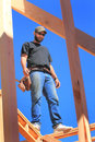 Framer at work on wall a carpenter wearing leather nail bags looking down standing in the rafters a working the roof of a house Royalty Free Stock Photo