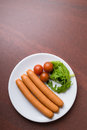 Frankfurter sausages three on a white plate Stock Photography