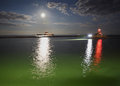 Fraser river night shift a dredger under a full moon on the near the mouth of steveston harbor a pilot boat returns to the harbor Stock Photo