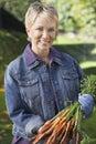 Frau die bündel von muddy carrots hält Stockfotos