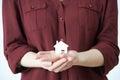 Frau die vorbildliches house in palm der hand hält Stockfotografie