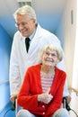 Frau doktor pushing happy elderly im rollstuhl Lizenzfreies Stockfoto