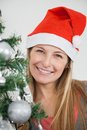 Frau in santa hat smiling by christmas baum Stockbilder