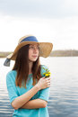 Freckled girl with bouquet standing on shore of the lake Royalty Free Stock Images