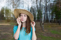 Freckled girl in hat listening to shell a and looking away Royalty Free Stock Images