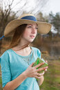 Freckled girl in hat standing with note and looking away windy weather Stock Photos