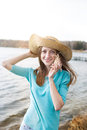 Freckled girl listening seashell in hat and smiling Stock Image