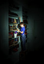 Freckled red-haired little boy searching book on bookcase Royalty Free Stock Photo