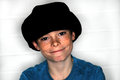 Freckles happy teenager boy with a lot of wearing a big black cap Royalty Free Stock Photography