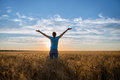 Free Happy Woman Enjoying Nature and Freedom Outdoor. Woman with arms outstretched in a wheat field in sunset.