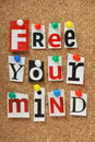 Free your mind the phrase in cut out magazine letters pinned to a cork notice board Royalty Free Stock Image