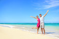 Freedom on beach vacation happy carefree couple winning with arms up showing happiness and fun paradise with perfect Royalty Free Stock Images