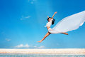 Freedom beautiful joyful girl with white tissue jumping against blue sky Royalty Free Stock Photo