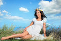 Freedom beautiful smiling brunette in white dress and flower wreath on head against blue sky Royalty Free Stock Images