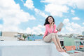 Freedom concept. Enjoyment. Asian young woman relaxing under blu Royalty Free Stock Photo