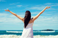 Freedom and happiness on summer vacation the beach joyful woman raising arms to the sky enjoying travel coast playa de verdicio Stock Photos