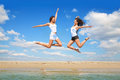 Freedom jump up of two joyful young women on sea beach against blue sky Royalty Free Stock Photography