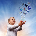 Freedom peace and spirituality boy releasing butterflies into the air concept for Stock Images