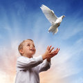 Freedom peace and spirituality boy releasing a white dove into the air concept for Stock Image