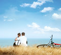 Freedom romantic young couple with bicycles on edge of coastline against blue sky Royalty Free Stock Photos