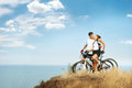 Freedom romantic young couple with sporty bicycles on edge of cliff against sky background Royalty Free Stock Images