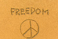 Freedom and a sign of peace  - inscription on sand beach. Royalty Free Stock Photo