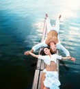 Freedom top view of beautiful young couple lying on small wooden bridge Stock Photography