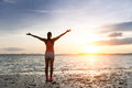 Freedom and tranquility at the beach on sunset sporty woman enjoying relax towards sun sea bliss concept Royalty Free Stock Photography