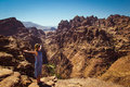 Freedom traveler woman standing with raised arms enjoying amazing mountain landscape. View from Petra to Wadi Araba desert. Hipste