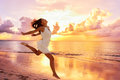 Freedom wellness happiness concept happy woman well being carefree asian feeling blissful jumping of joy on peaceful beach at Royalty Free Stock Images