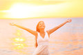 Freedom woman happy and free open arms on beach at sunny sunset beautiful joyful elated looking up smiling by the ocean Stock Image