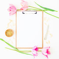Freelancer or blogger workspace with clipboard, notebook, pink tulips and accessories on white background. Flat lay, top view. Royalty Free Stock Photo