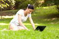 Freelancer is always ready to work girl in the park doing interesting talk on the laptop Stock Images
