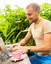Freelancer working in park man sitting at rough country wooden desk on computer drinking coffee business dress code Royalty Free Stock Image