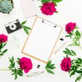 Freelancer workspace with clipboard, dairy, peony flowers, retro camera on white background. Flat lay, top view. Beauty blog conce