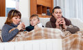 Freezing family of three warming near warm radiator with cups tea in home Royalty Free Stock Photography