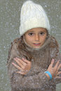 Freezing girl with bobble hat and turtleneck jumper outside in snow Stock Images