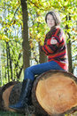 Freezing woman sitting on sawn tree trunk and hugging herself Royalty Free Stock Photo