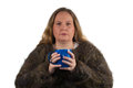 Freezing woman with tea cup a is cold and wears warm clothing an drinks or coffee Stock Image