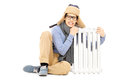 Freezing young guy in winter hat and scarf sitting next to radia radiator isolated on white background Royalty Free Stock Photo