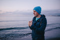 freezing young man on the beach. Man feels freeze rubs and warms her hands. Royalty Free Stock Photo