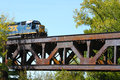 Freight Train Crossing a Steel Railroad Truss River Bridge Stock Images