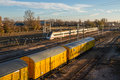 Freight train routes between moving and cars freshly painted yellow on the tracks with sunset light Stock Images