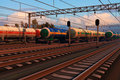 Freight trains with fuel tank cars in sunset Royalty Free Stock Photo