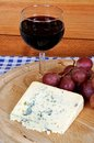 French blue cheese with wine bleu d auvergne red and red grapes on a wooden board Royalty Free Stock Photo