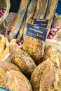French breads with generic price signs on red checked cloth in French market. Royalty Free Stock Photo