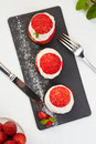French Cakes with strawberry cream shanti. aery brewing cake on black shale. Restaurant composition on white background. Royalty Free Stock Photo