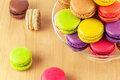 French colorful macarons in a glass cake stand traditional on wooden table Royalty Free Stock Photo
