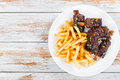 French fries with fried sticky ribs sprinkled with green onion Royalty Free Stock Photo